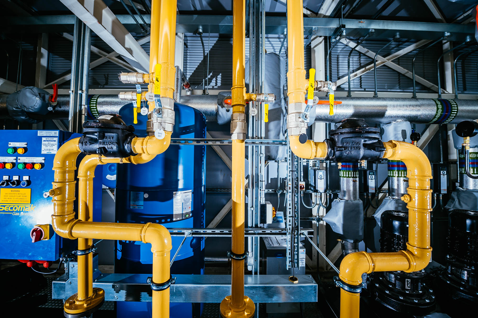 A photo of yellow and blue pipework at above an art gallery