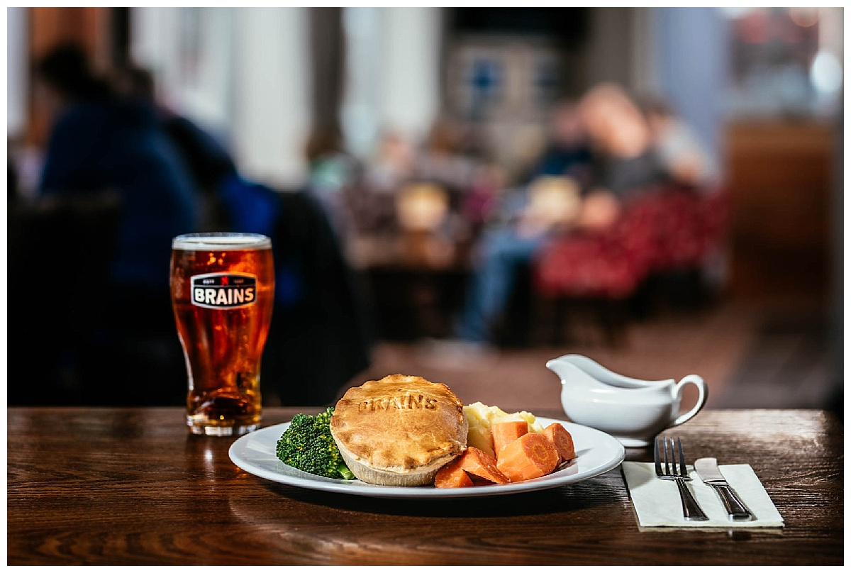 A photo of a pie with vegetables on a table with a pint of brains beer with a pub in the background