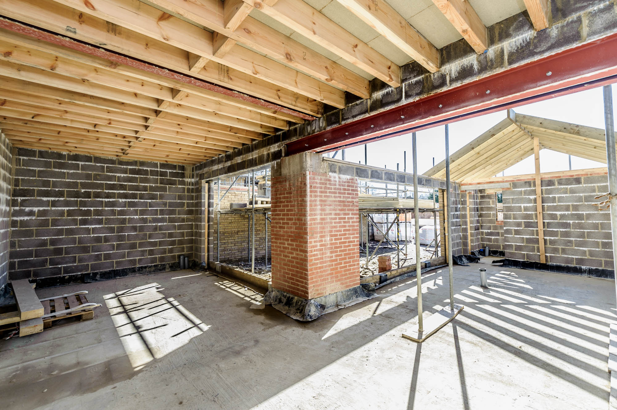 A photo of the interior of a house during the building stage showing beams, bricks and lintels