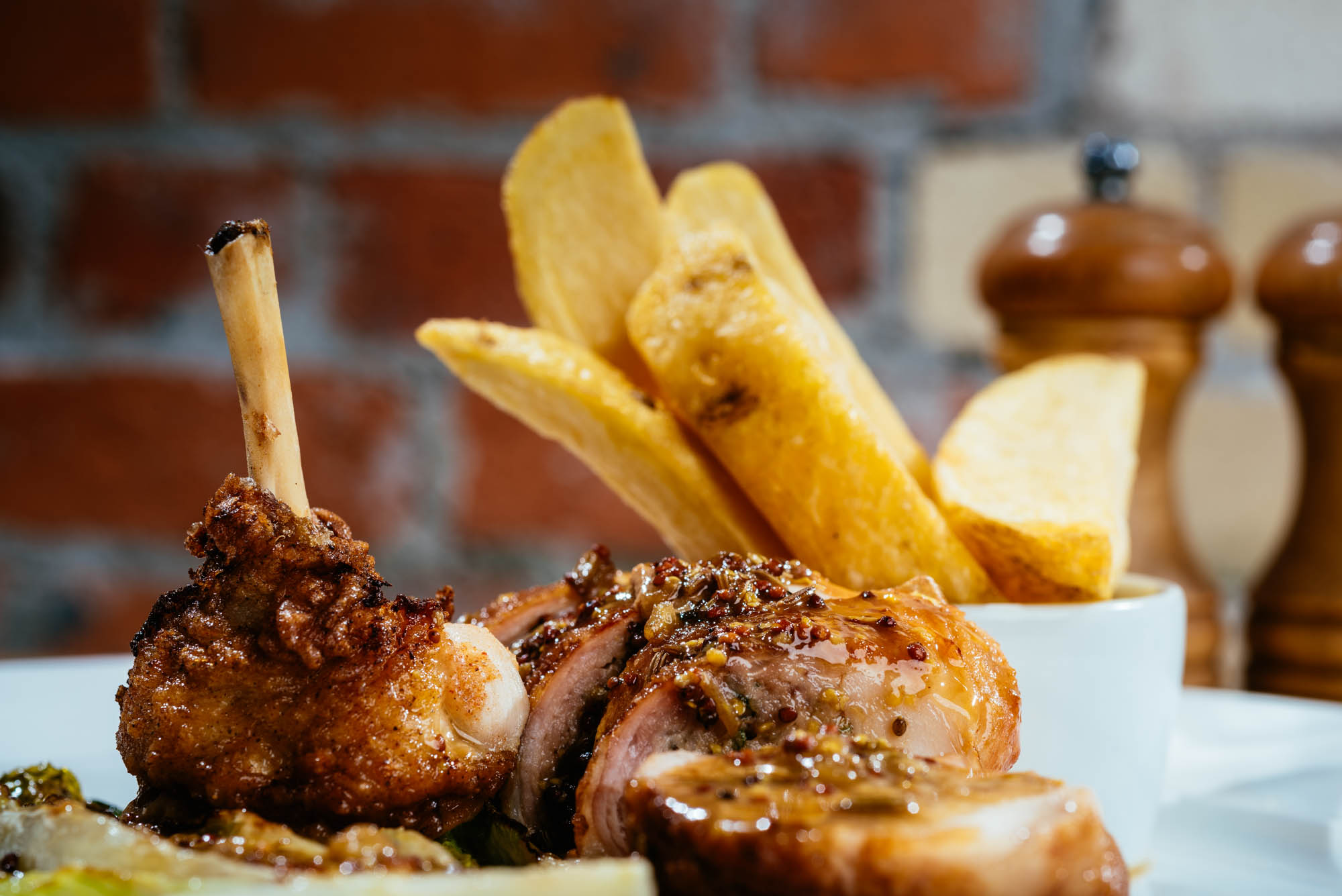 A photo of meat and chips on a plate in front of a red brick wall