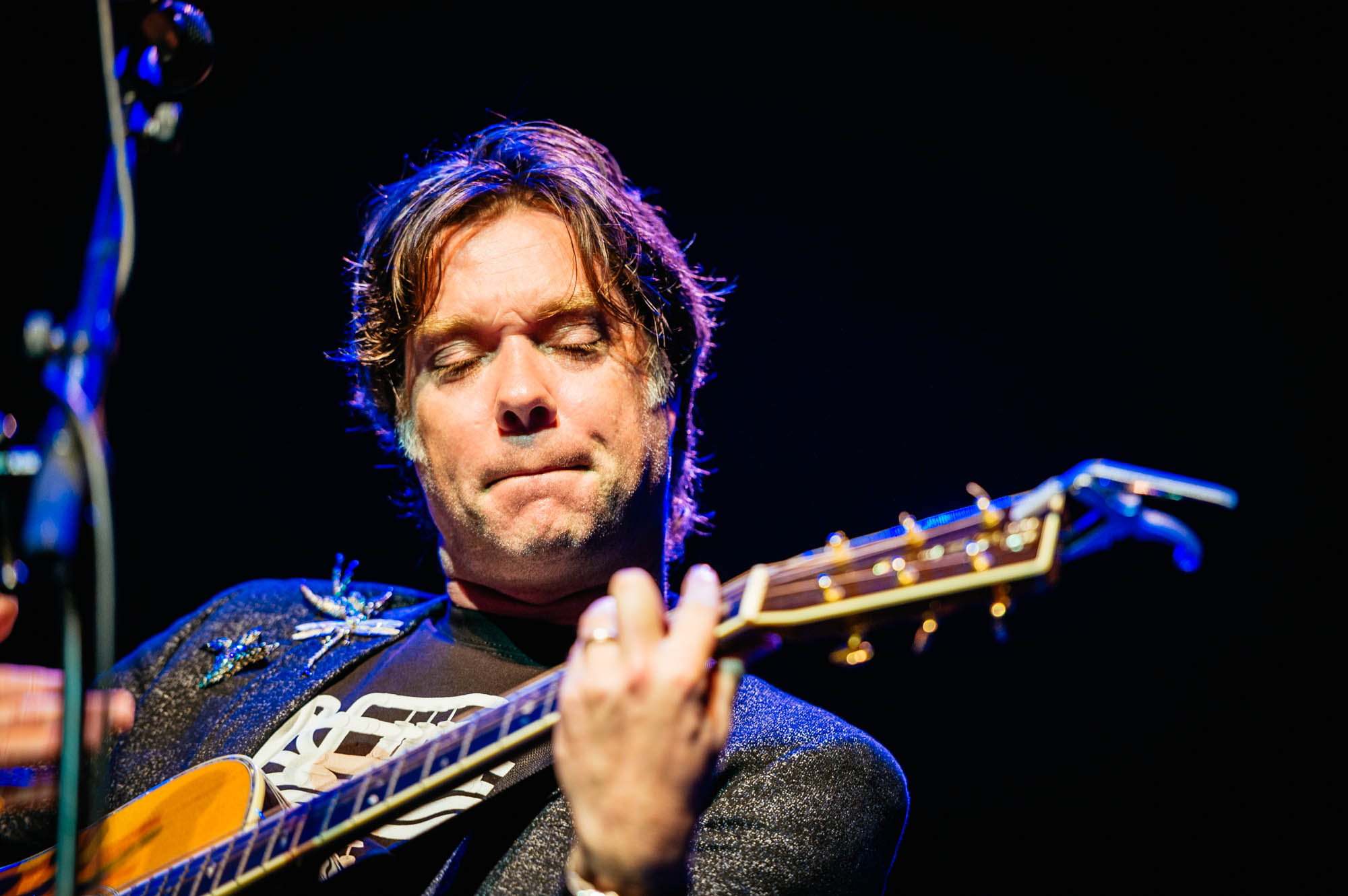 A photo of Rufus Wainwright at the Festival of Voice onstage playing a guitar
