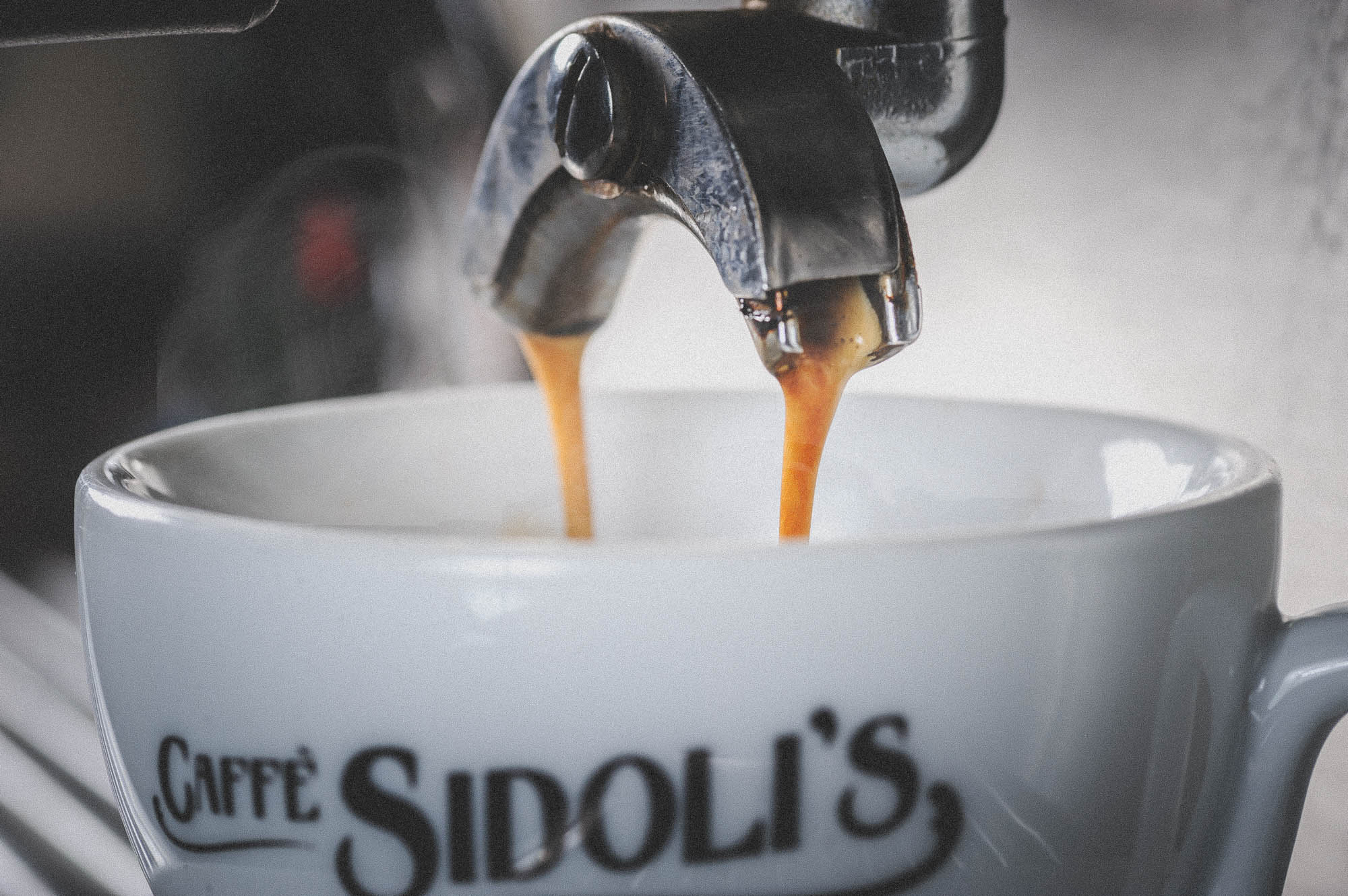 A photo of espresso coffee pouring and steaming into a cup