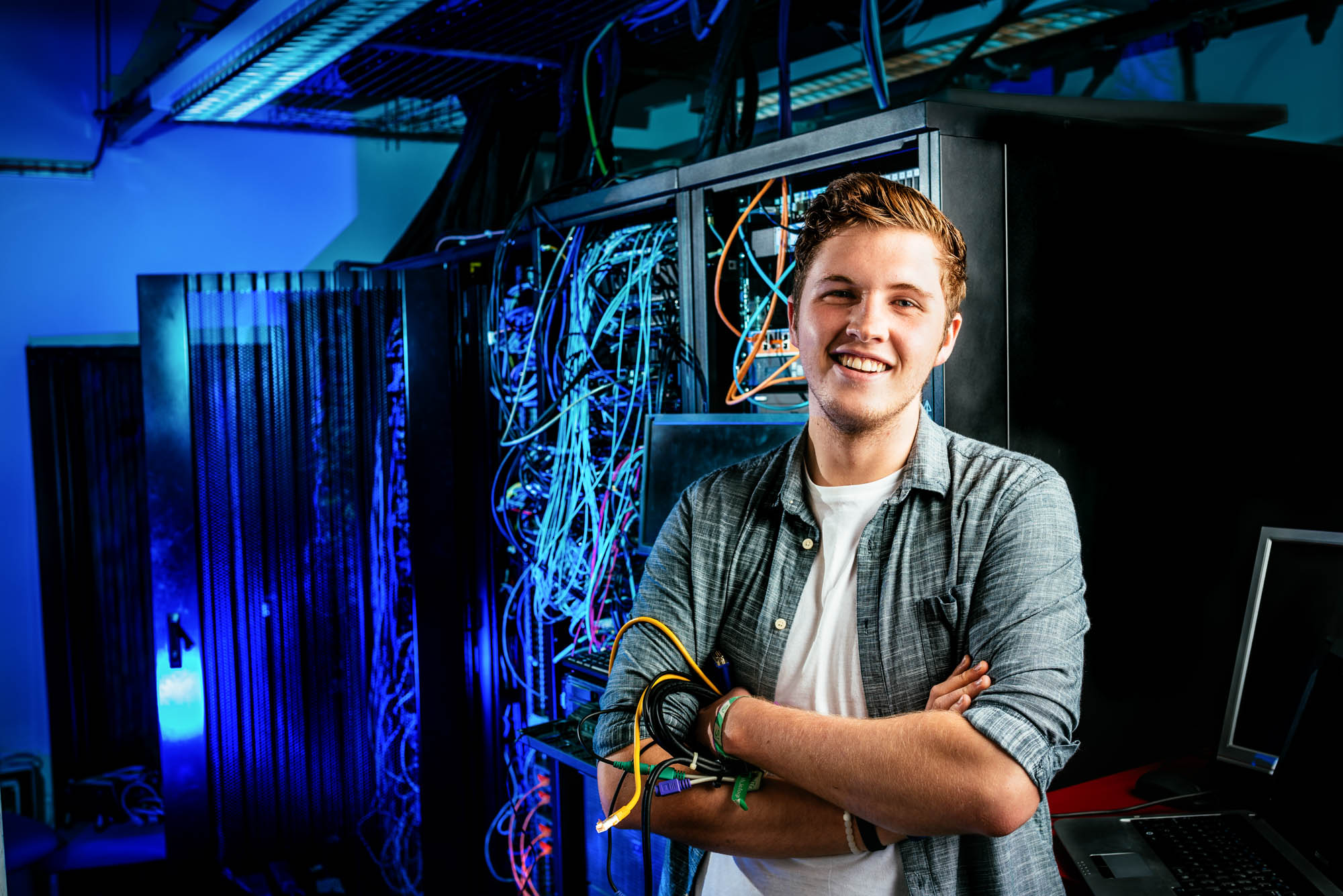 A photo of an IT student holding cables in front of a large networking cabinet