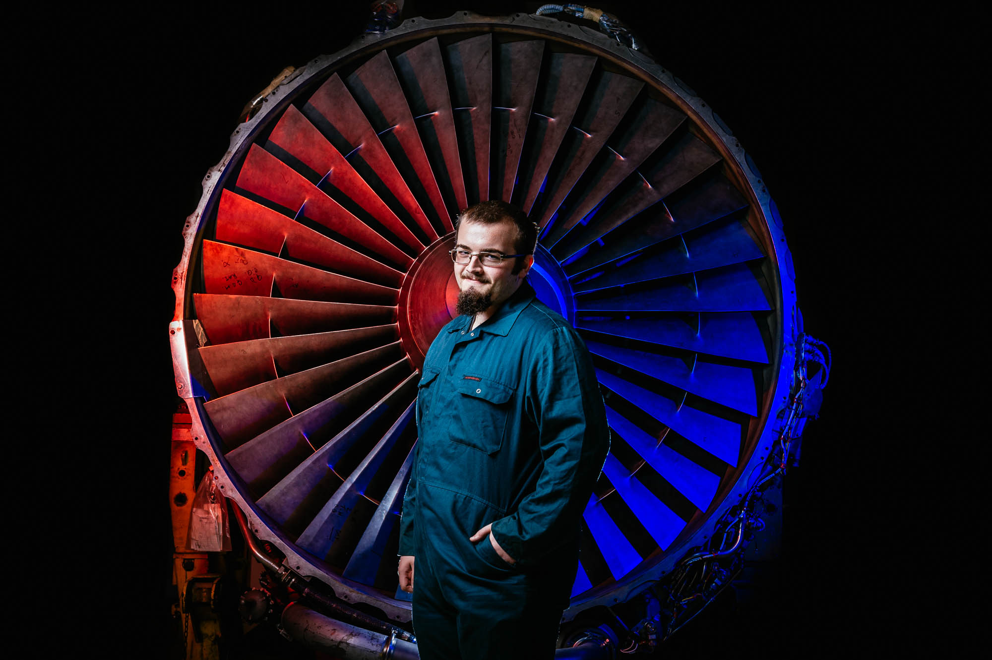 A photo of an engineering student standing in front of a jet propeller