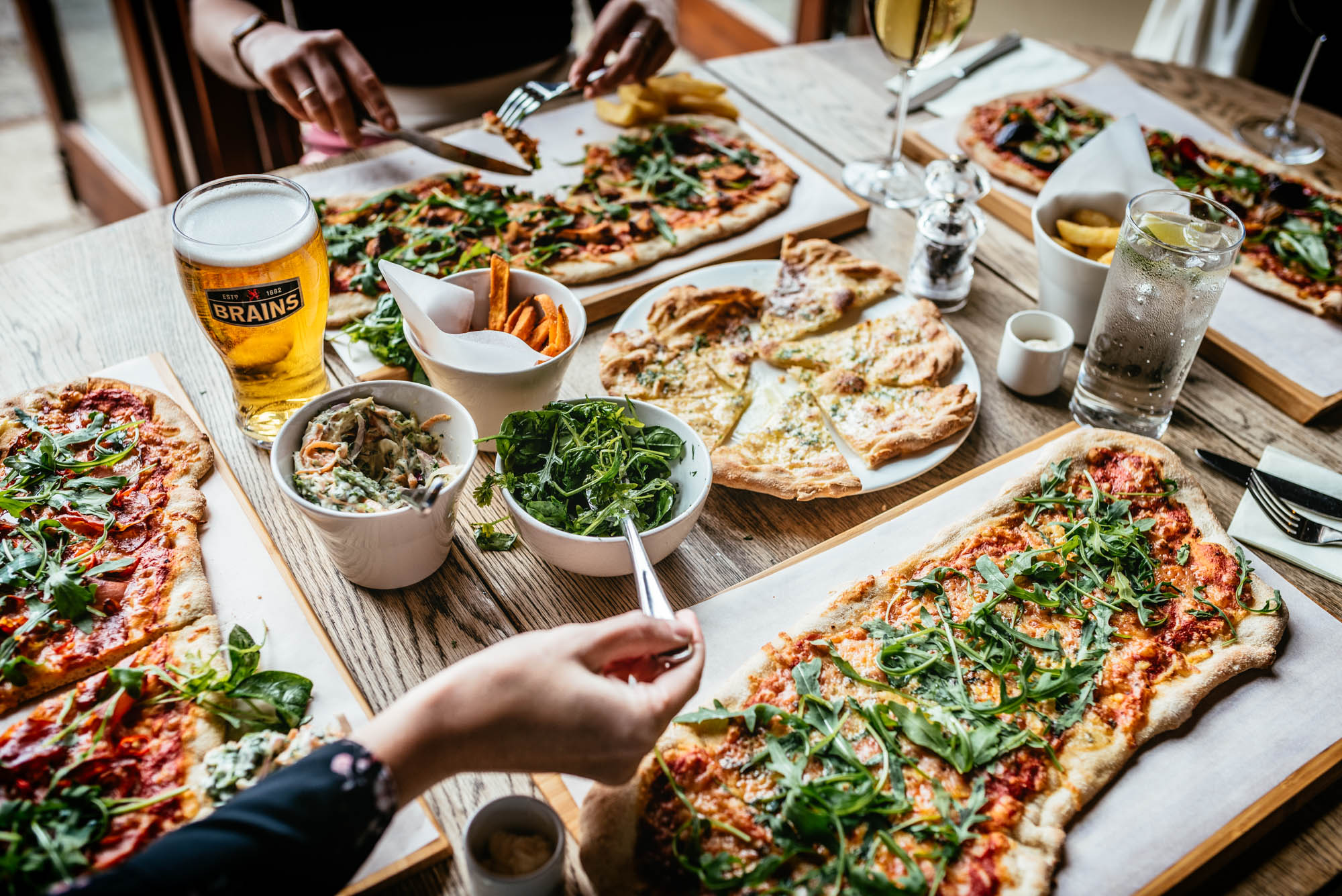 A photo of a table of food in a pub with four people sharing pizza, coleslaw, garlic bread and with drinks of beer, wine and sparkling water