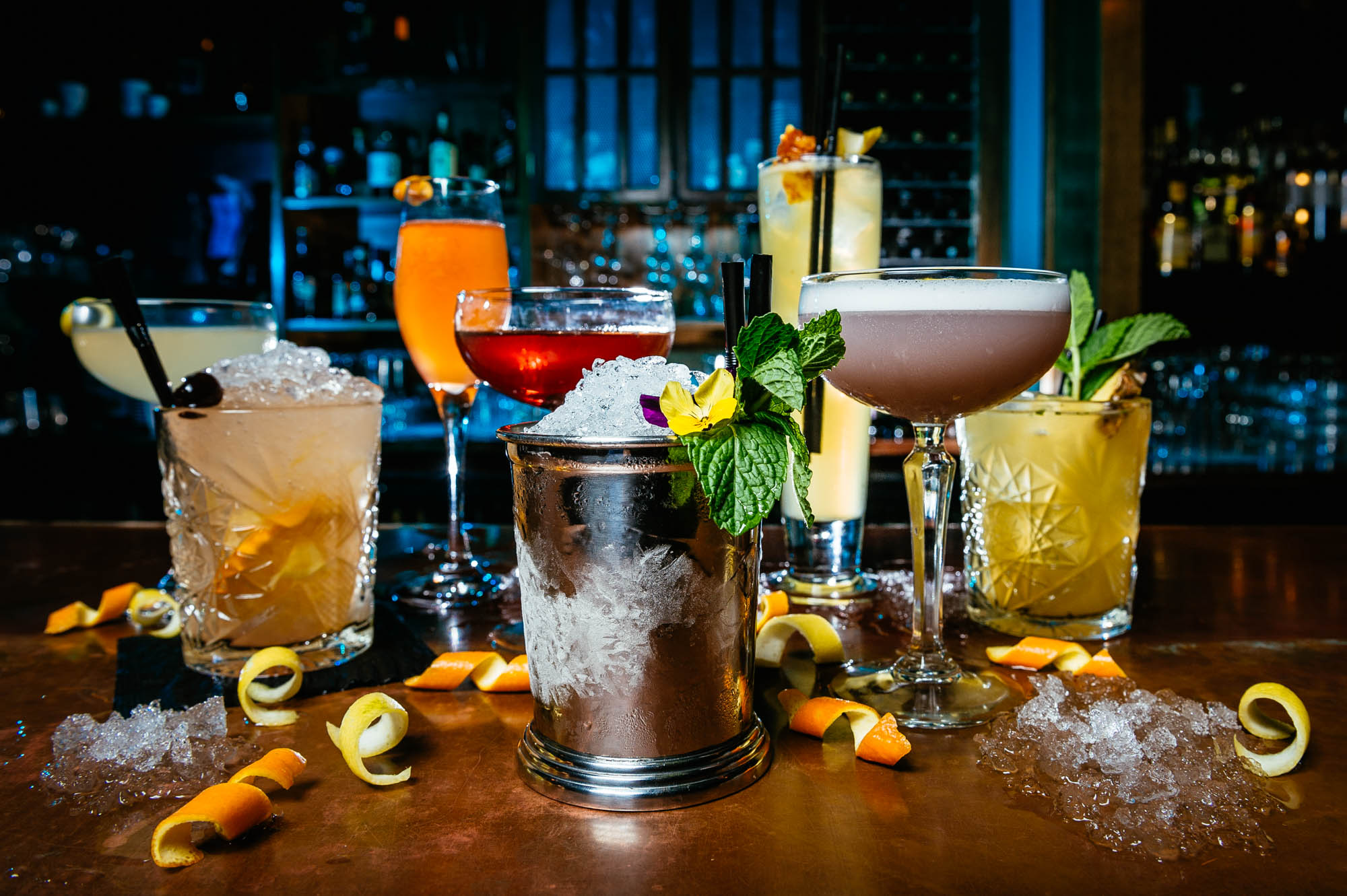 A photo of a set of seven different cocktails on a bar