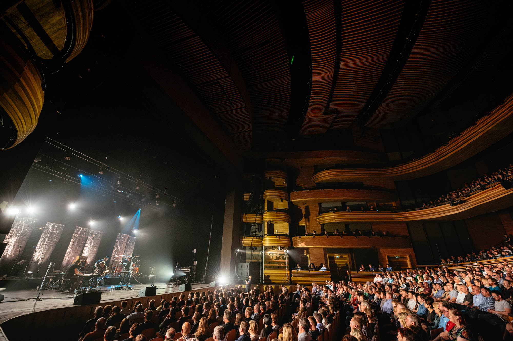 A photo of the inside of the Wales Millennium Centre Auditorium with a full house audience and stage Lighting