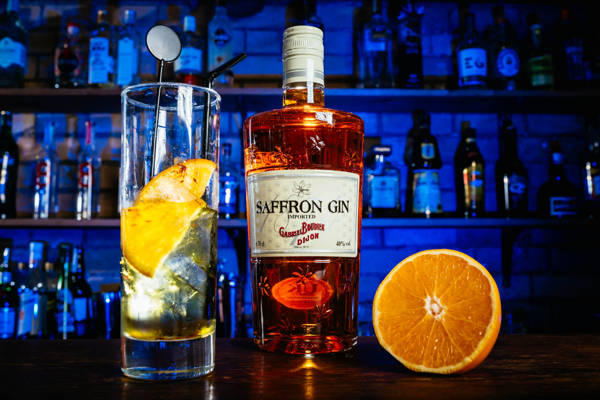 A photo of a bottle of saffron gin with a glass and a sliced orange in front of a blue lit bar