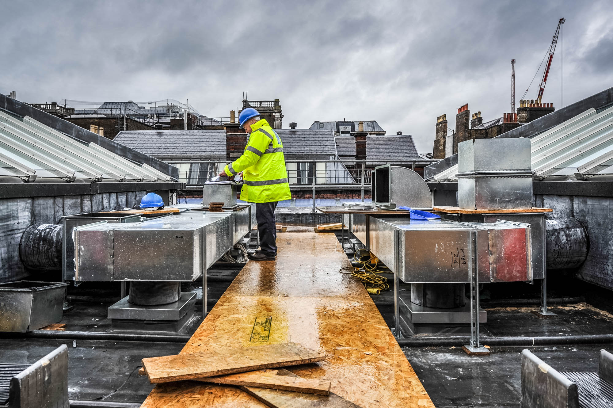A photo of an architect reviewing plans on the rooftop of a building in central london