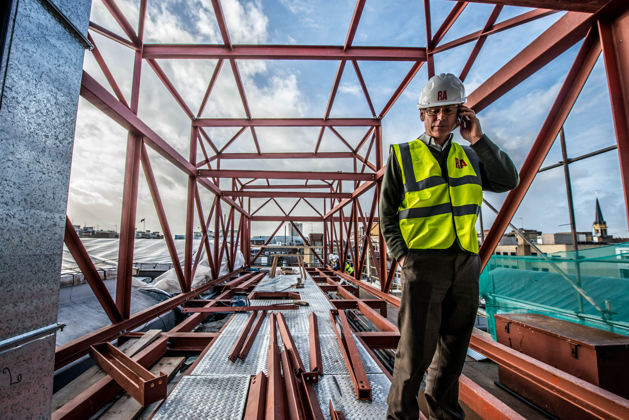 A photo of an manager engineer taking a phone call whilst stood in a building steel project with the london city skyline as the backdrop